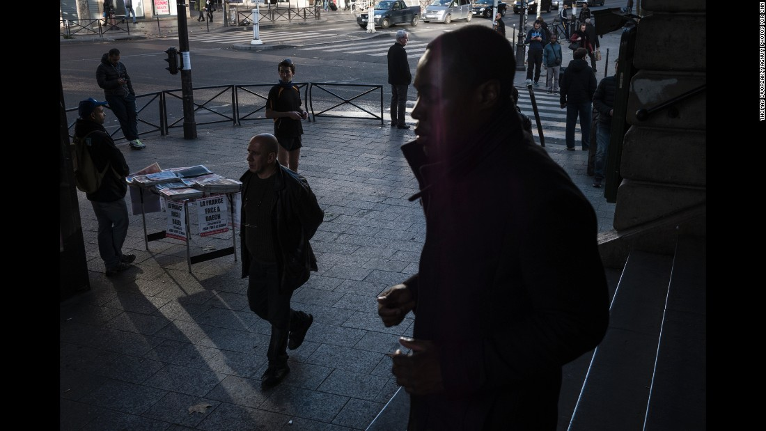 "A man sells newspapers on Sunday, November 15, at the Barbes-Rochechouart Metro station in one of the Paris neighborhoods with the highest foreign-born population. The headlines read ""The War against Daech / ISIS"" and ""The Day After."""