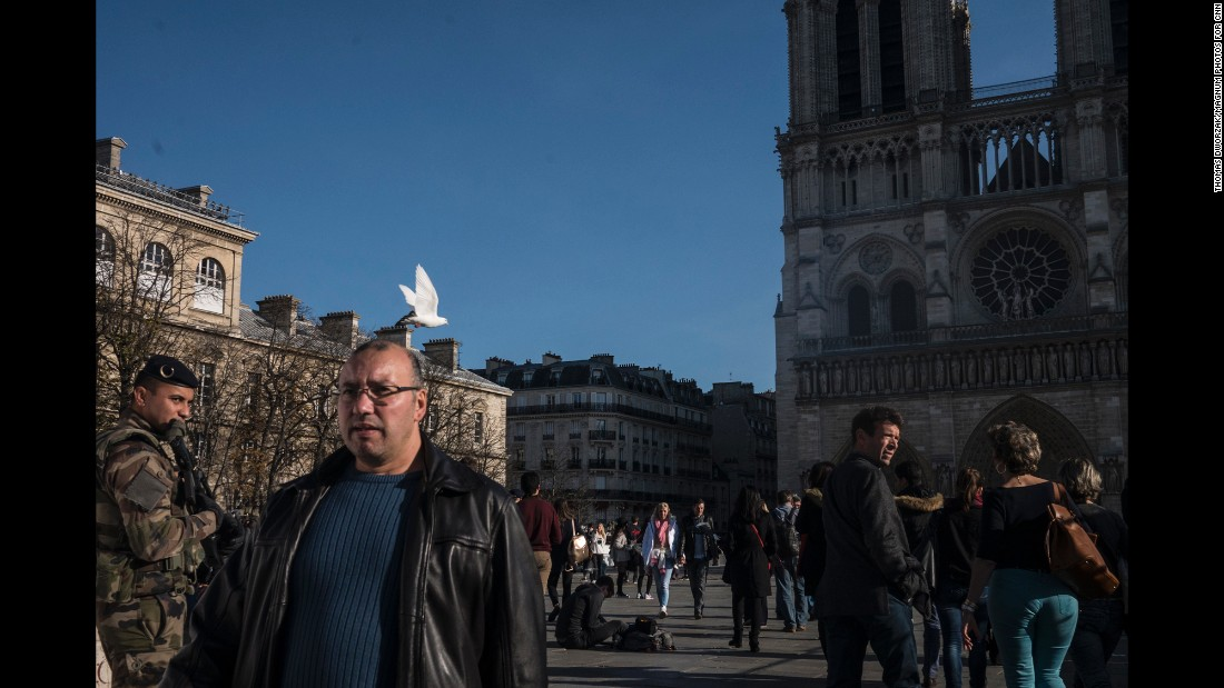 Tourists walk past Notre Dame on November 15 as the military and police patrol the area.