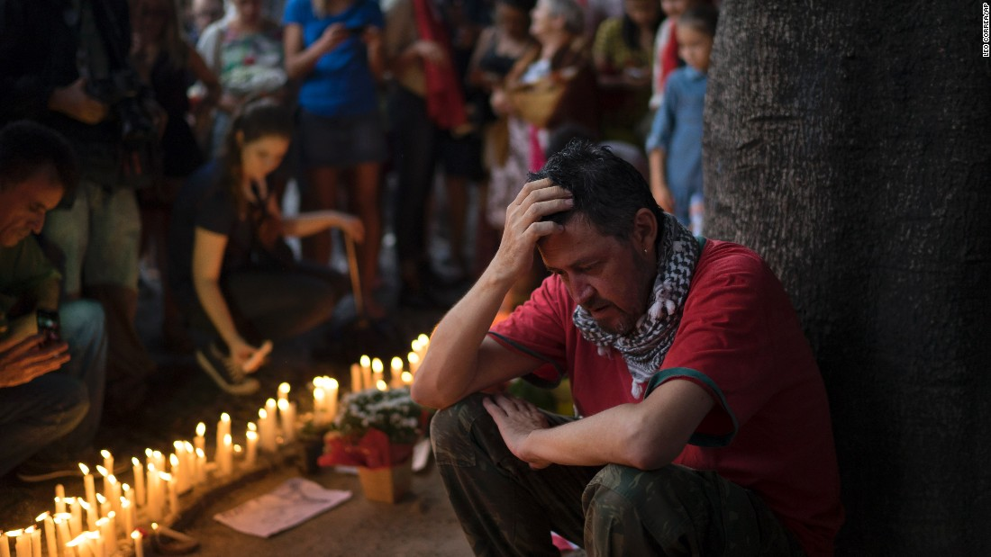 A man sits next to candles lit as homage to the victims of the deadly attacks in Paris at a square in Rio de Janeiro on November 15.