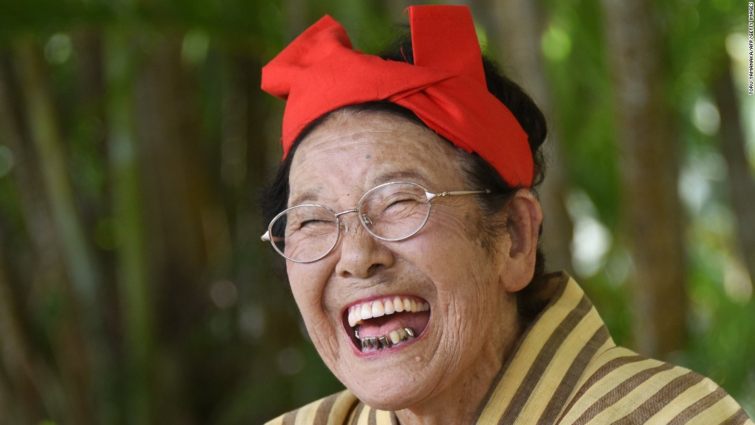 Tomi Menaka, a 92-year-old member of a singing and dancing troupe, laughs during a performance on Japan's Kohama Island on Monday, June 22.