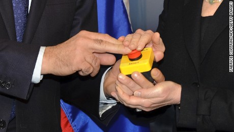 "The hands of US Secretary of State Hillary Clinton and Russian Foreign Minister Sergei Lavrov rest on a red button marked ""reset"" in English and ""overload"" in Russian that US Secretary of State Hillary Clinton handed to Russian Foreign Minister Sergei Lavrov during a meeting in March  2009."