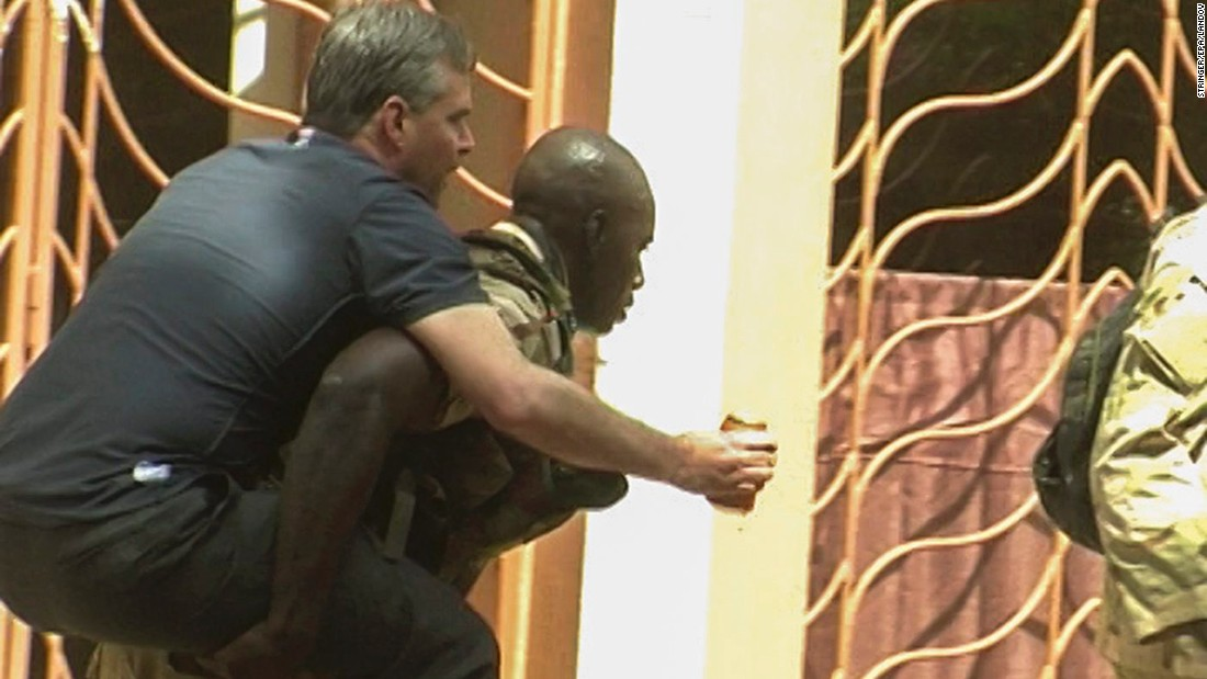 An injured, rescued hostage is carried from the hotel on November 20.