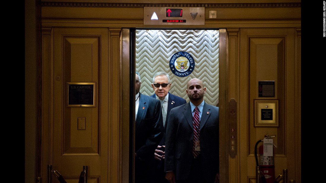 "Senate Minority Leader Harry Reid, in the sunglasses, boards an elevator at the Capitol after signing a condolence book Tuesday, November 17, for victims of <a href=""http://www.cnn.com/2015/11/13/world/gallery/paris-attacks/index.html"" target=""_blank"">the Paris terrorist attacks.</a>"