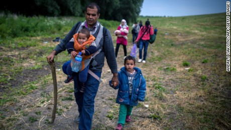 "A group of migrants from Syria walk towards the border with Hungary, near the northern Serbian village of Martonos, near Kanjiza, on June 25, 2015.Hungary said it has indefinitely suspended the application of a key EU asylum rule in order ""protect Hungarian interests"", prompting Brussels to seek immediate clarification."