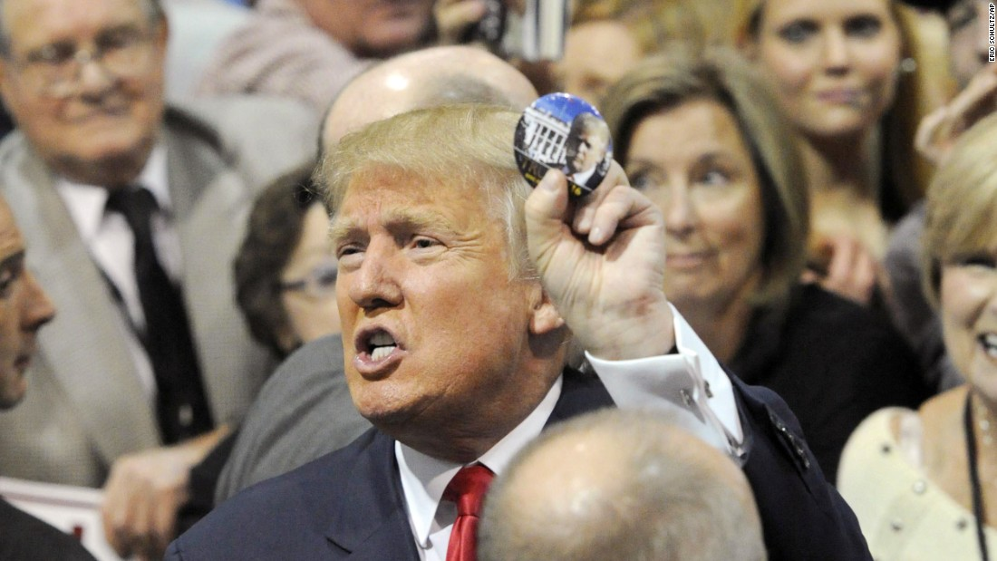 Republican presidential candidate Donald Trump holds up a campaign button after speaking at a campaign stop on Saturday, November 21, in Birmingham, Alabama.