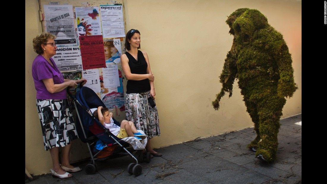 "<strong>June 7:</strong> A ""moss man"" marches during the Corpus Christi procession in Bejar, Spain. The annual procession commemorates Christians who used moss as camouflage to hide from Muslim guards and re-conquer the town in the 12th century."