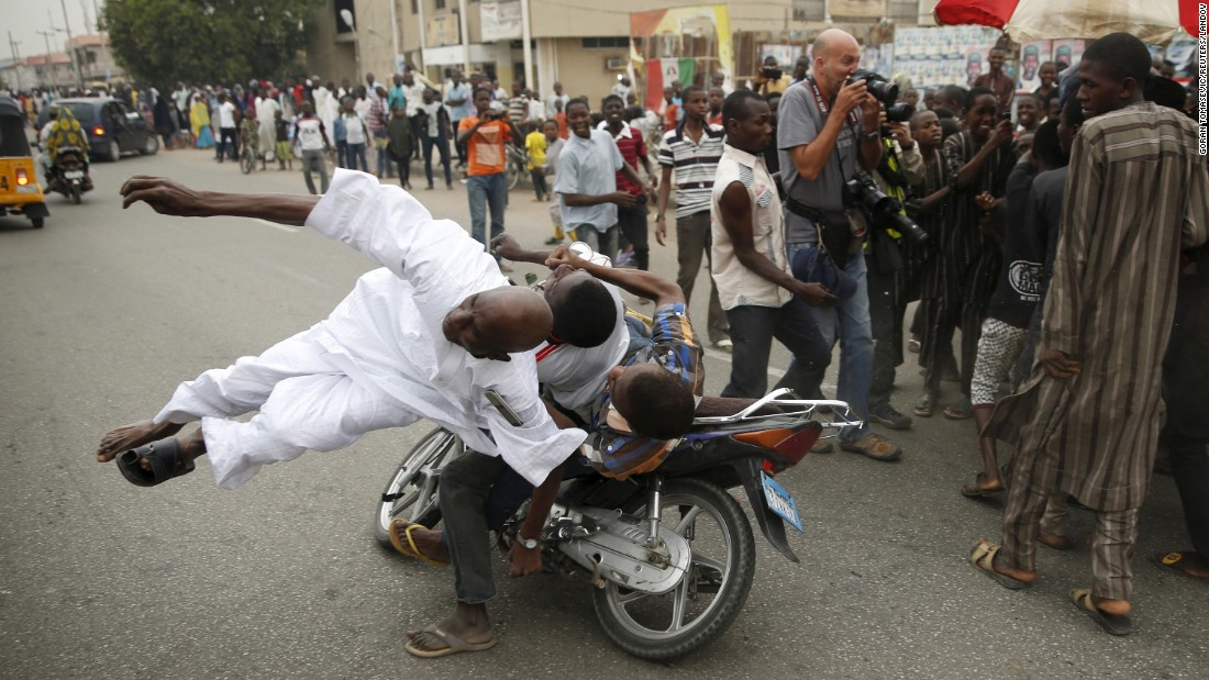 <strong>March 31:</strong> A supporter of Nigerian presidential candidate Muhammadu Buhari is hit by another supporter on a motorbike during celebrations in Kano, Nigeria. Buhari defeated incumbent Goodluck Jonathan.