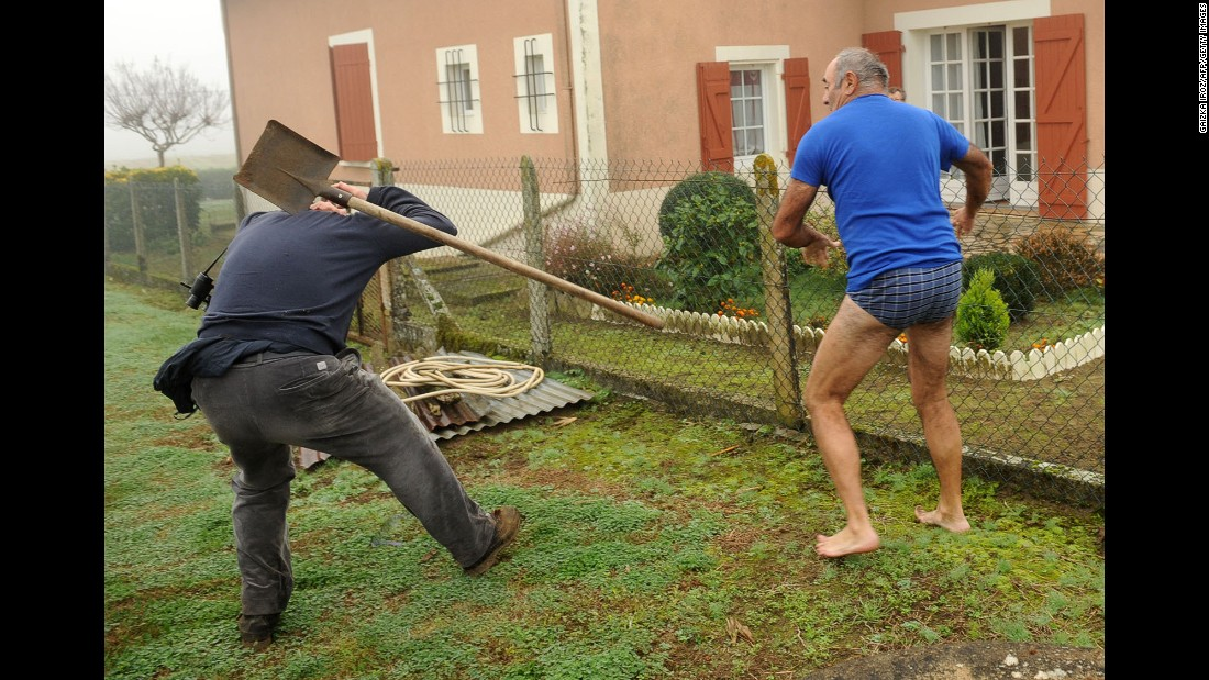 <strong>November 9:</strong> A member of the Bird Protection League, left, is hit by a spade thrown by the owner of a plot where finch traps were found in Audon, France. Wildlife activists were trying to disable the traps.