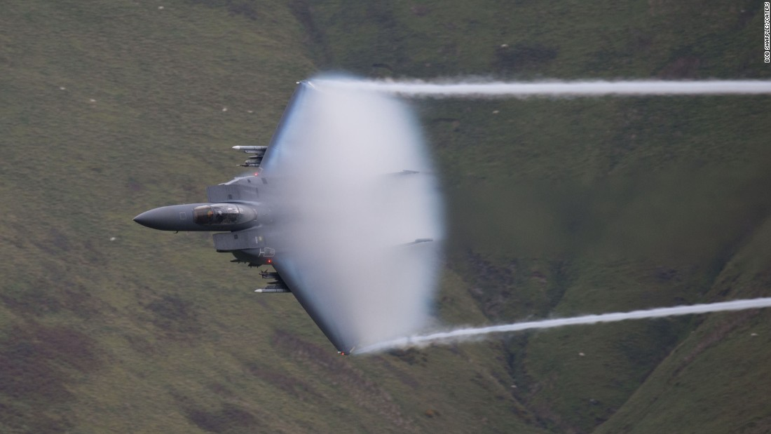 <strong>October 8: </strong>A low-flying jet zooms through a picturesque valley in Wales, leaving a vapor cloud in its wake.