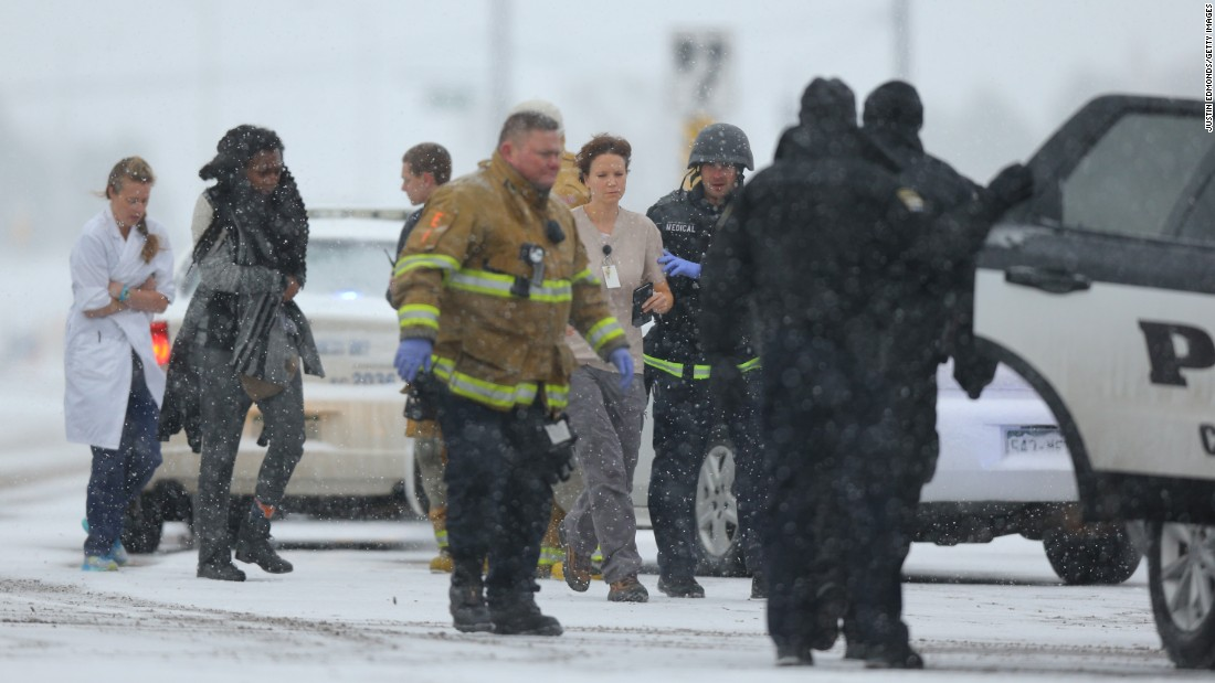 People are escorted to an ambulance during the standoff.