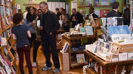 US President Barack Obama taks with manager Anna Thorn while shopping with daughters Malia and Sasha in Upshur Street Books during Small Business Saturday on November 28, 2015, in Washington, DC.