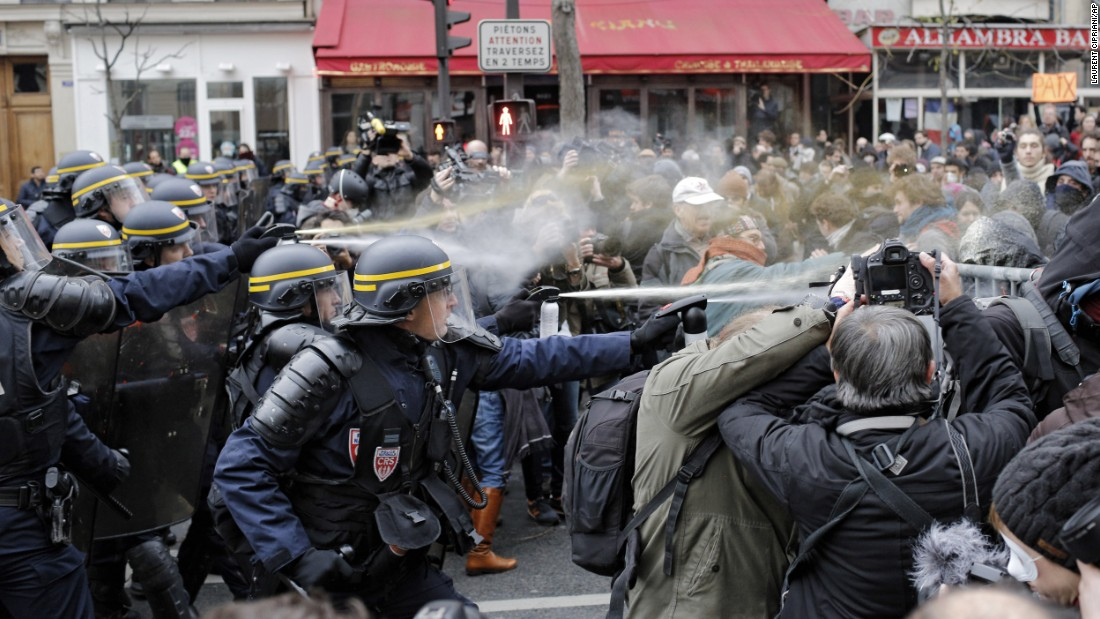 Police fight with activists during a protest ahead of the 2015 Paris Climate Conference at the Place de la République.