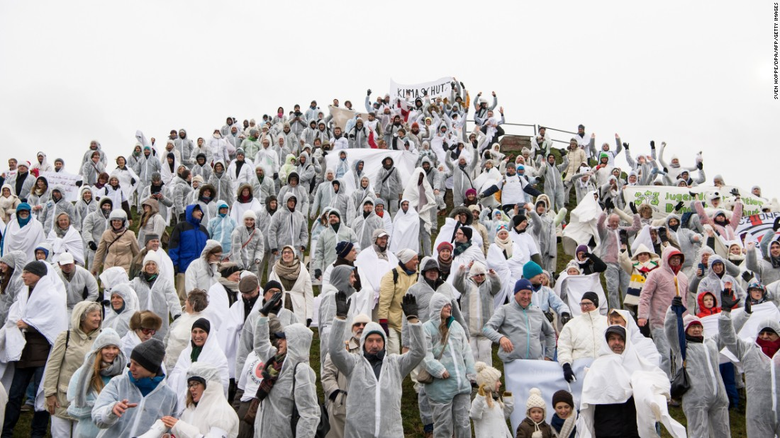 People dressed in white crowd form a human glacier in Munich, Germany.