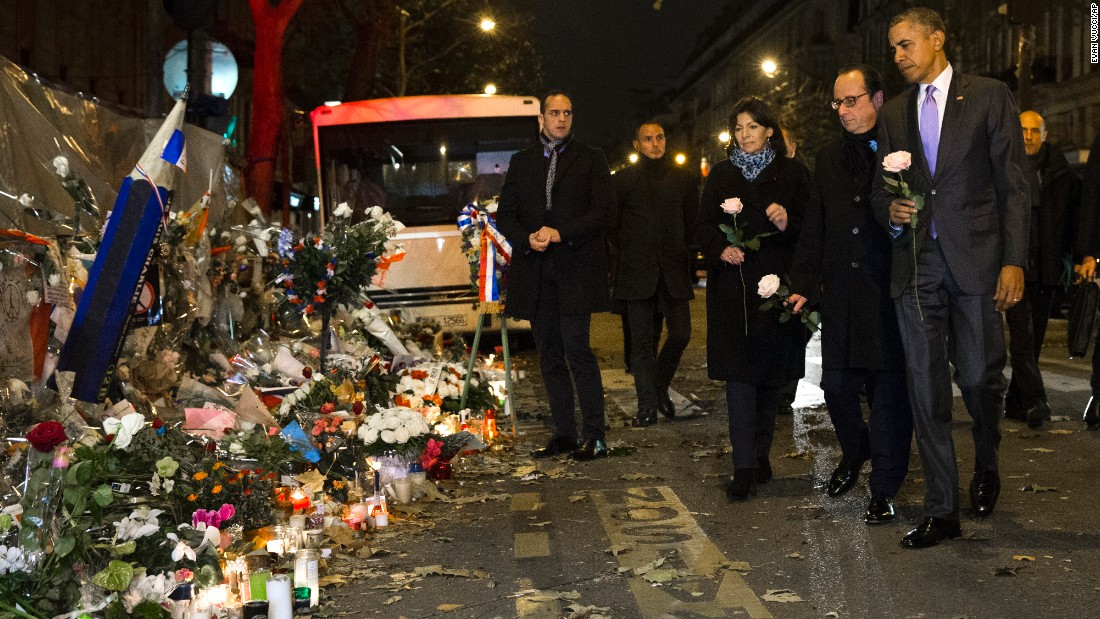 President Barack Obama, French President Francois Hollande, second from right, and Paris Mayor Anne Hidalgo arrive at the Bataclan, site of one of the Paris terrorists attacks, to pay their respects to the victims after Obama arrived in town for the COP21 climate change conference early on Monday, November 30, in Paris.