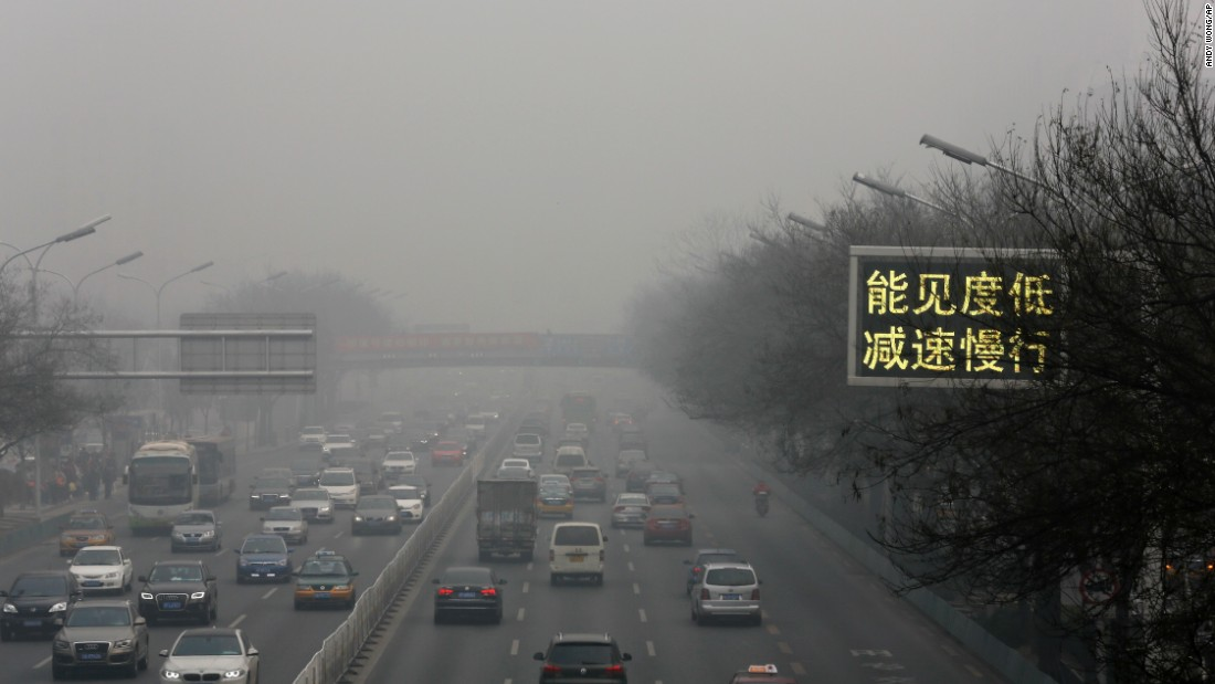 "Vehicles drive along a highway in Beijing with a traffic sign that reads ""Slow down, low visibility"" on November 30."