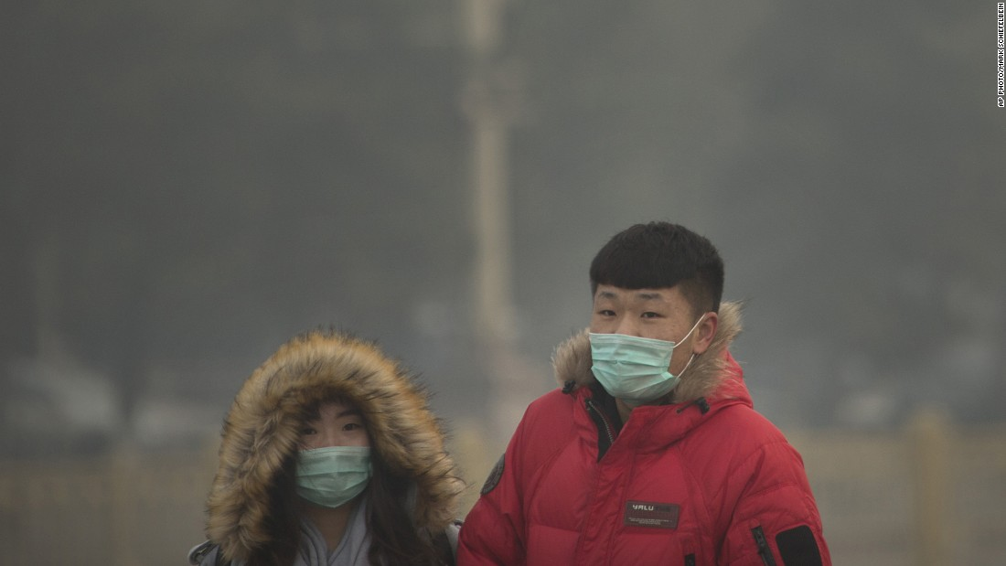 People wearing face masks walk across Tiananmen Square in Beijing on November 28.