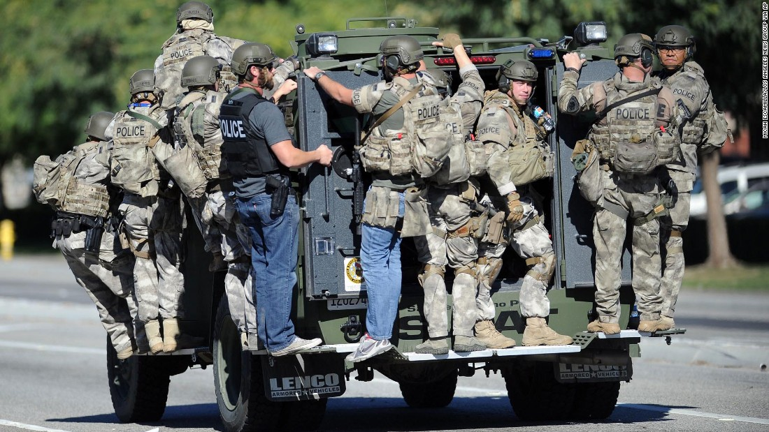 A SWAT vehicle carries police officers.