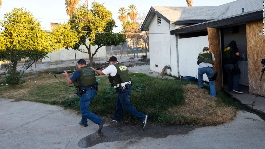 Law enforcement officers search a residential area for suspects who fled after the shooting.