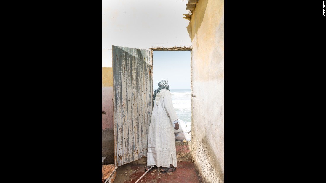 A man looks out at the sea through a door that once led to another room of his house. He and his family moved furniture out the front door, while the sea chewed at the back.