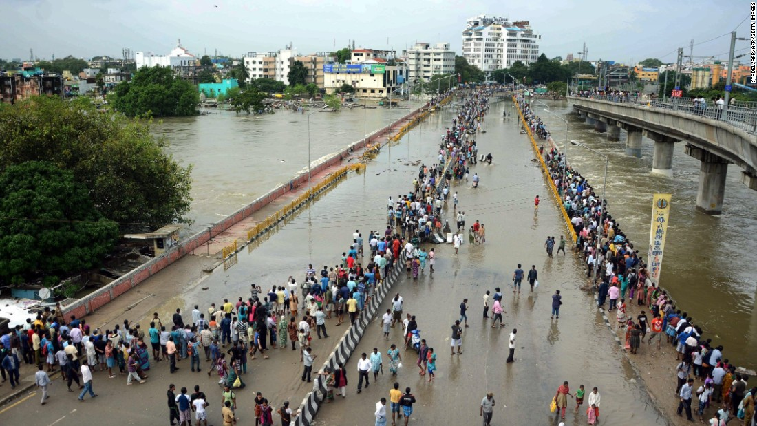 Residents look at flood water on a major highway in Chennai on December 3.