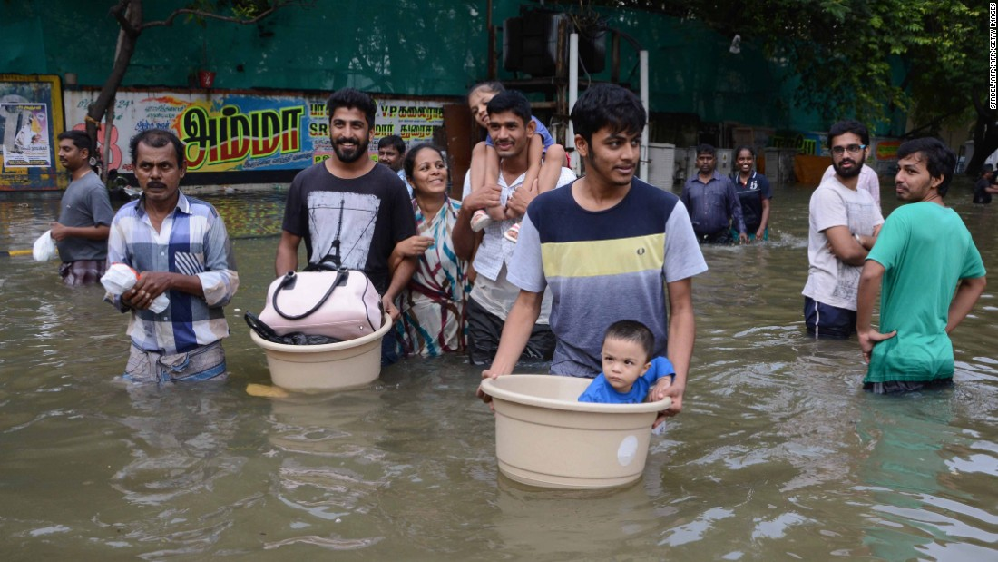 Indian residents carry children and possessions as they walk through flood waters in Chennai  December 3.