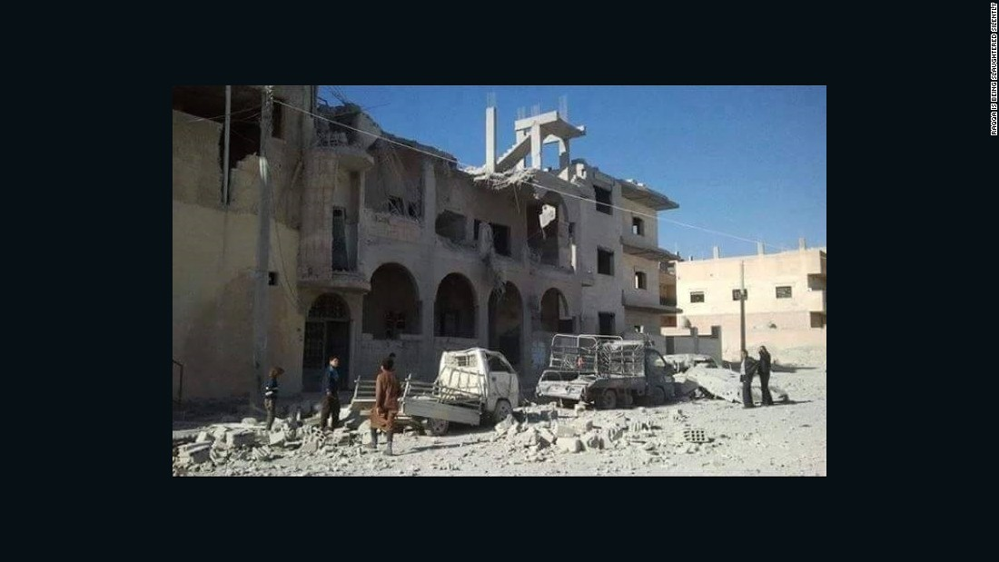 In this photo from November 29, 2015, provided to CNN by the activist group Raqqa is Being Slaughtered Silently, residents assess the damage to a building in the northern Syrian city -- ISIS's headquarters -- which has been the target of French airstrikes in recent weeks.