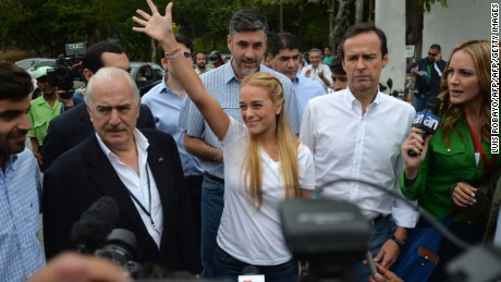 Venezuelan opposition leader and wife of jailed leader Leopoldo Lopez, Lilian Tintori (C) waves as she arrives accompanied by former Colombian president Andres Pastrana (L) and former Bolivian president Jorge Quiroga (2nd-R) to vote at a polling station in Caracas, on December 6, 2015. Venezuelans voted Sunday in tense elections that could see the opposition seize legislative power from the socialist government and risk sparking violence in the oil-rich, cash-poor nation.. AFP PHOTO/LUIS ROBAYO / AFP / LUIS ROBAYO        (Photo credit should read LUIS ROBAYO/AFP/Getty Images)