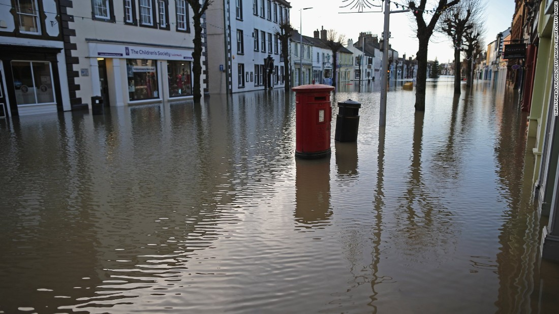 Water rises near a post box in Cockermouth, December 6.