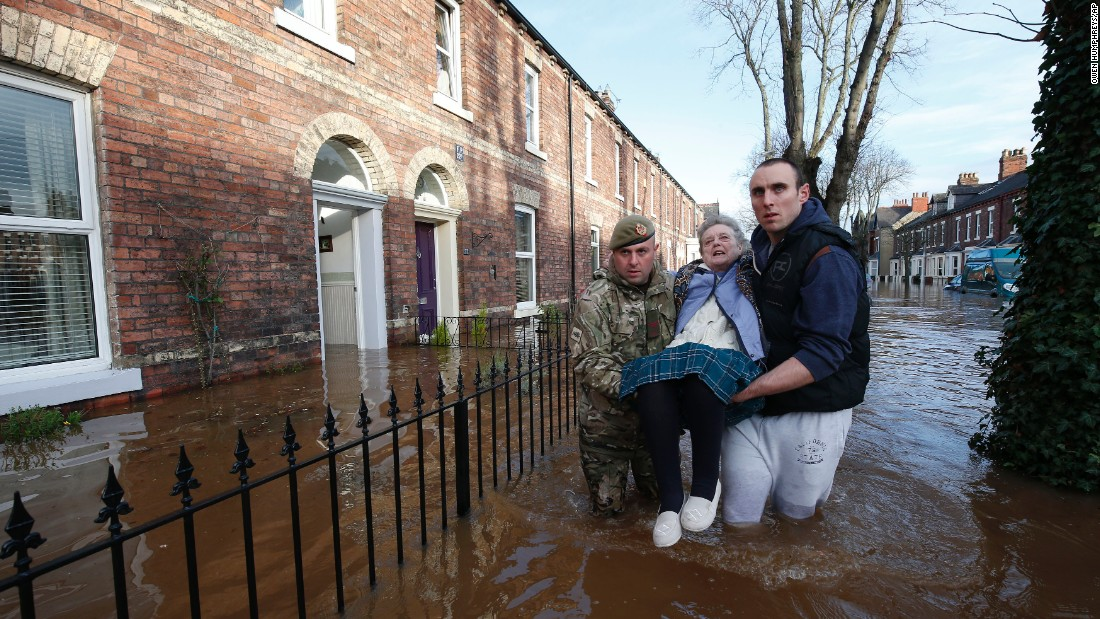 Margaret McCraken, 79, is helped from her home in Carlisle, northern England on December 6, 2015 by members of the armed forces. Storm Desmond whipped across Britain at the weekend, bringing heavy rain, strong winds and flooding to parts of the country.