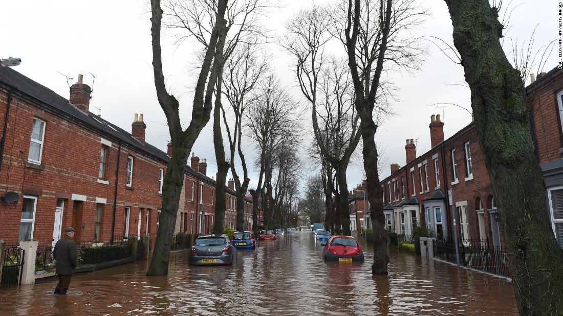 A man walks down a flooded street in Carlisle, England on December 6.