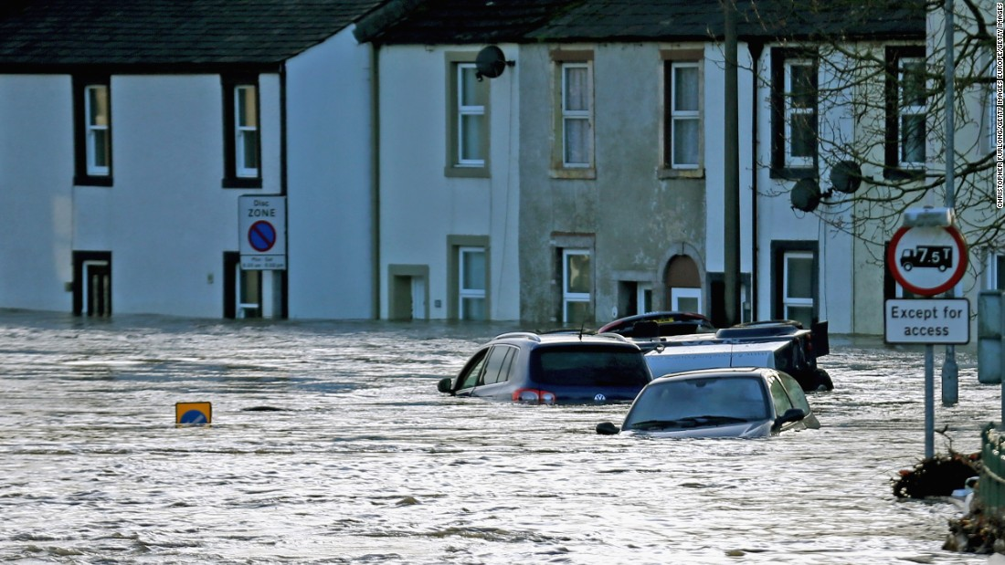 Flood water engulfs cars in the town of Cockermouth, northern England.