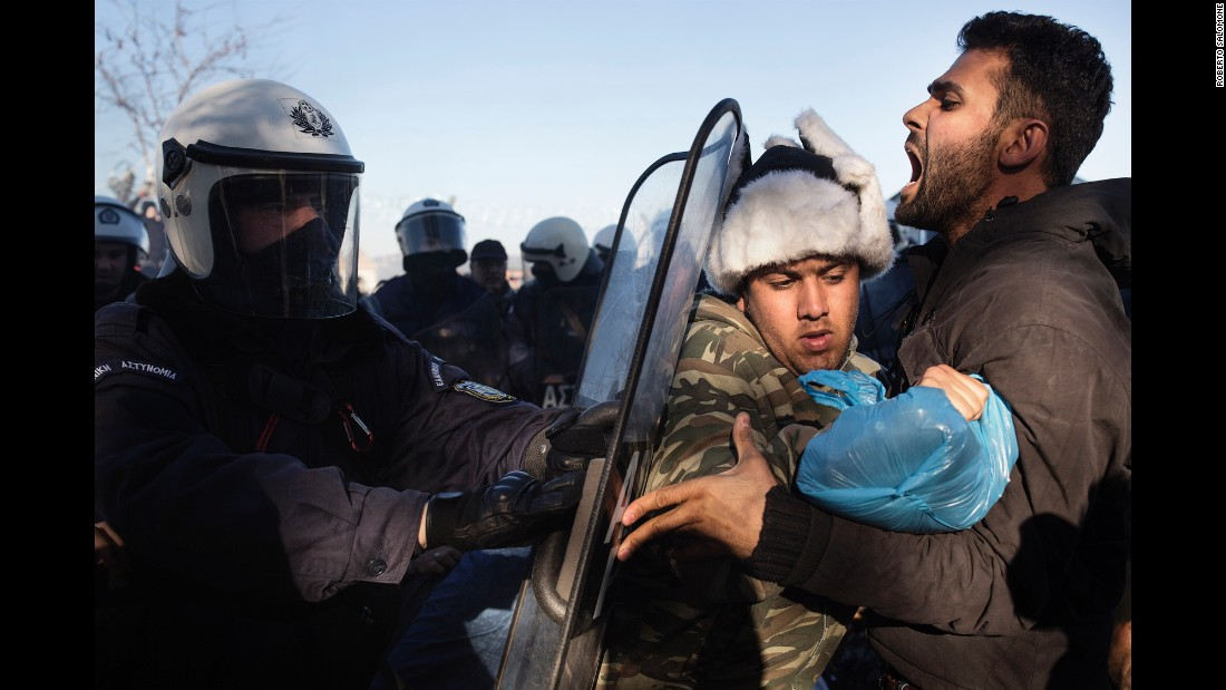 Greek anti-riot police try to remove a group of migrants at the border on December 4. Only Syrians, Afghans and Iraqis are permitted to enter neighboring Macedonia. Immigrants from places like Iran and Pakistan are rejected.