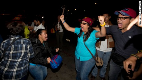 Opposition supporters celebrate in Caracas, Venezuela,  early Monday Dec. 7, 2015.  Venezuela's opposition won control of the National Assembly by a landslide on Sunday, delivering a major setback to the ruling party and altering the balance of power after 17 years of socialist rule.