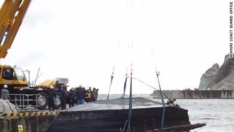 Japanese coast guard pull the wooden boat from the water.
