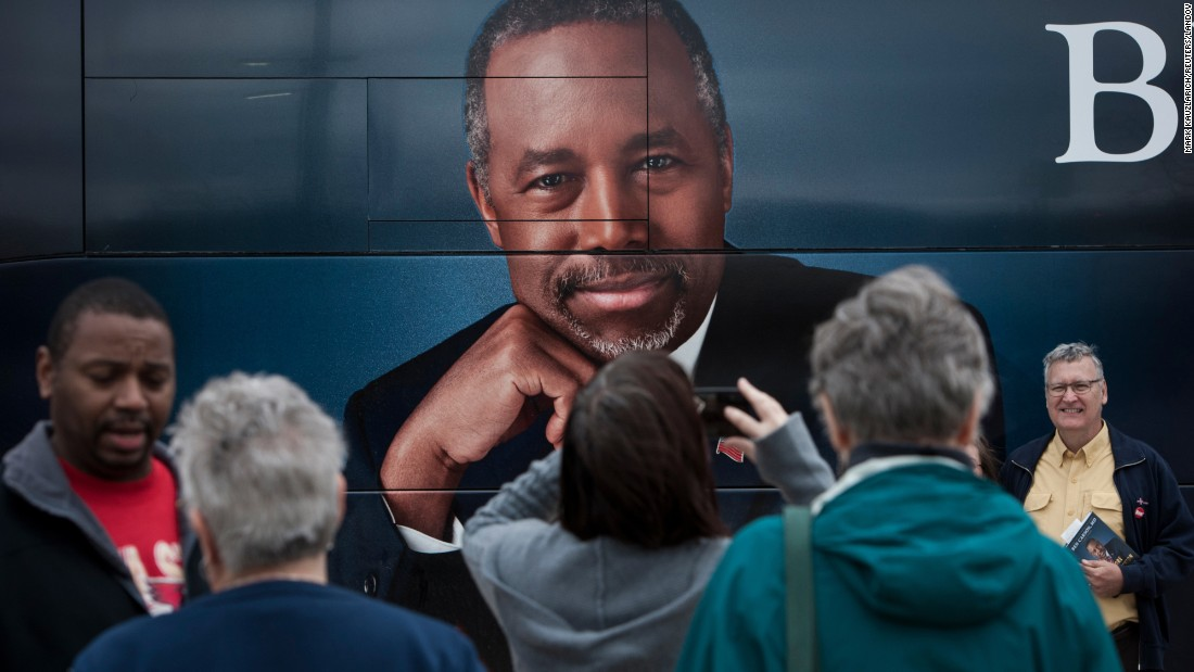 Supporters of Republican presidential candidate Ben Carson stand in front of his tour bus at a book signing in Edmond, Oklahoma, on Wednesday, October 21.