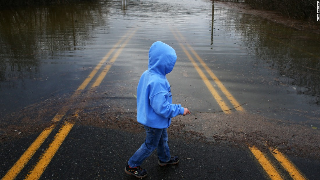 A 5-year-old boy walks on a flooded street outside of Duvall, Washington, on December 9.