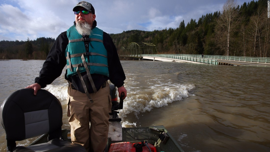 Jeff Limb steers his boat through a flooded area of the Snoqualmie River, near the Tolt Hill Bridge in Carnation, Washington, on December 9.
