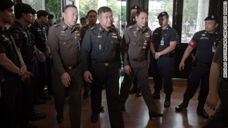 Thai Army Lt. Gen. Manas Kongpan, center, is surrounded by police as he turns himself in at police headquarters in Bangkok on June 3, 2015.