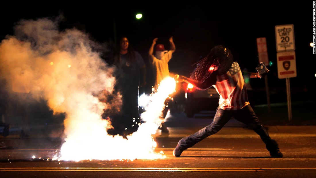 A demonstrator throws back a tear gas container as police try to break up a group of bystanders in Ferguson, Missouri, on August 13, 2014. The photo was one of a group that won a Pulitzer for the St. Louis Post-Dispatch Photography Staff. The photographer used a Canon digital camera, with various lenses from 35mm to 55mm.
