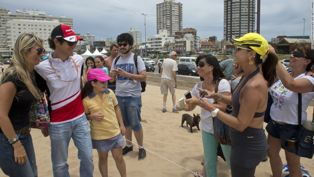 Mahindra Racing's star driver Bruno Senna poses with fans on the sand at the Punta del Este resort in 2014.