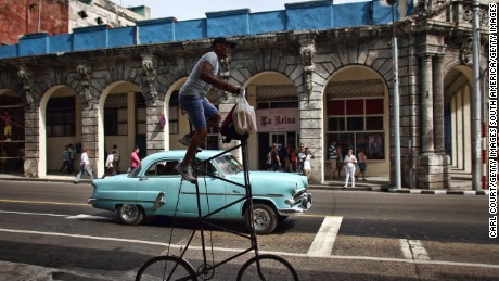 HAVANA, CUBA - SEPTEMBER 16: A man rides his modified bicycle past a vintage American car on September 16, 2015 in Havana, Cuba. Pope Francis is due to make a three day visit to Cuba from September 19 where he will meet President Raul Castro and hold Mass in Revolution Square before travelling to Holguin, Santiago de Cuba, El Cobre and onwards to the United States.  (Photo by Carl Court/Getty Images)