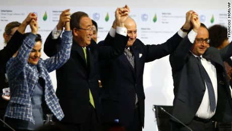 French President Francois Hollande, right, French Foreign Minister and president of the COP21 Laurent Fabius, second, right, United Nations climate chief Christiana Figueres and United Nations Secretary General Ban ki-Moon hold their hands up after the final conference at the COP21, the United Nations conference on climate change, in Le Bourget, north of Paris, Saturday, Dec.12, 2015. Governments have adopted a global agreement that for the first time asks all countries to reduce or rein in their greenhouse gas emissions. (AP Photo/Francois Mori)