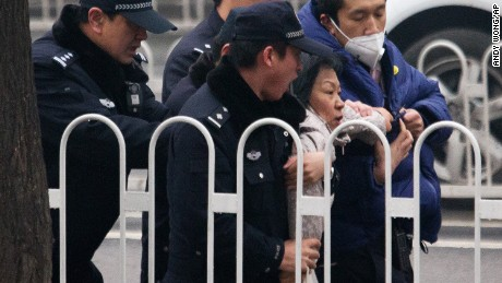Police officers take away a supporter of Pu Zhiqiang.