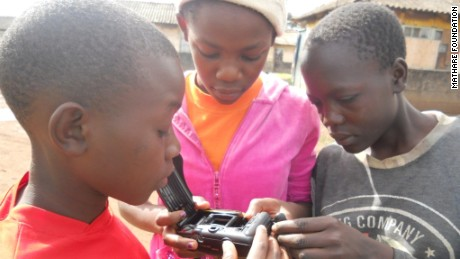 Children play with one of the Mathare Foundation's cameras