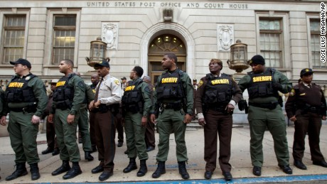 Officers stand guard in front of the courthouse main entrance as demonstrators protest after a mistrial of Officer William Porter, one of six Baltimore city police officers charged in connection to the death of Freddie Gray, on Wednesday, December 16.