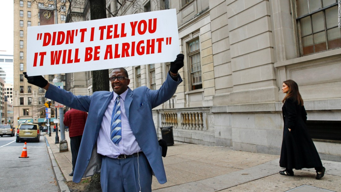 A man displays a sign outside of the courthouse during jury deliberations on December 16.