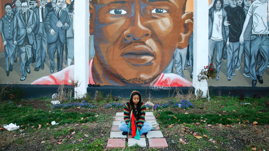 "A woman on December 16 sits below a mural depicting Gray at the intersection of his arrest. Bill Murphy, an attorney for the Gray family, stressed that the hung jury doesn't mean Porter's case is over. ""I don't buy the nonsense that this is somehow a victory for either side. It's not,"" he told reporters. ""It's just a bump on the road to justice, and you know, the road to justice has lot of bumps."""