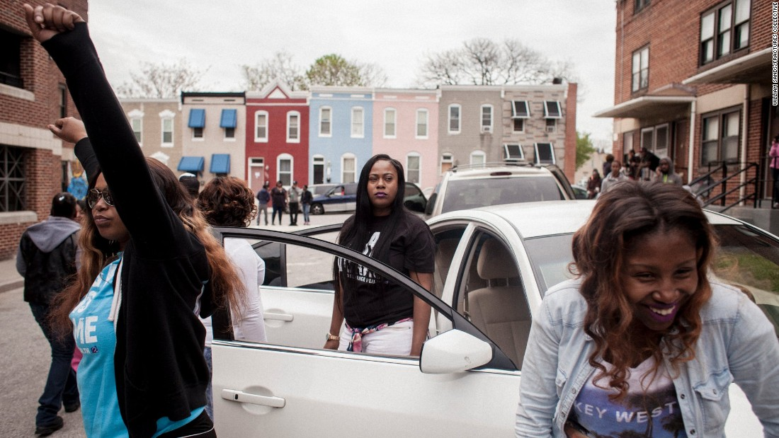 Women dance in front of their cars during the recording of a music video in memory of Freddie Gray.