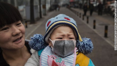 "A Chinese infant wears a mask in Beijing, which was on ""red alert"" for heavy pollution, in 2015."