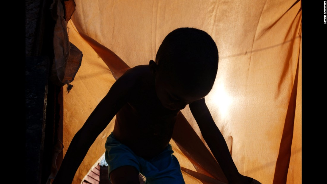 A child comes out of a tent where he lives with his family near Jardim Gramacho, a former landfill that was shut down in 2012.